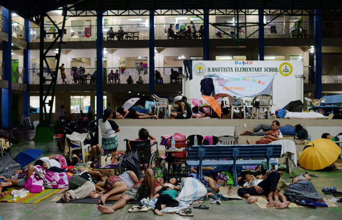 Residents, displaced by flash floods caused by monsoon rains, sleep on the floor of a basketball court in Marikina, Metro Manila, in Philippines, Reuters/UNI