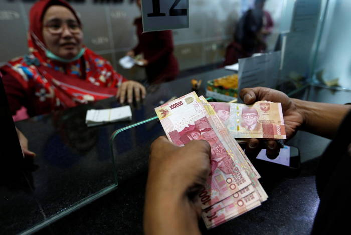 A customer holds Indonesian rupiah bank notes at a money changer in Jakarta, Indonesia, Reuters/UNI