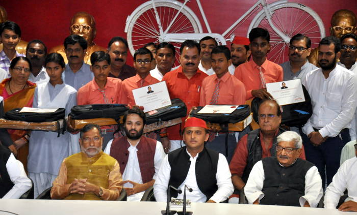 Samajwadi Party President Akhilesh Yadav with meritorious students after distributing 'laptops' at the party office in Lucknow, UNI