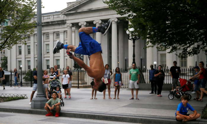 A street performer flips through the air in front of the US Treasury building as tourists and passersby look on in Washington, US, Reuters/UNI
