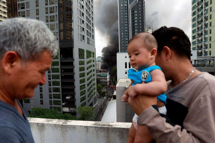 A family stands on top of a building as it looks at smoke from a fire in central Bangkok, Thailand, Reuters/UNI