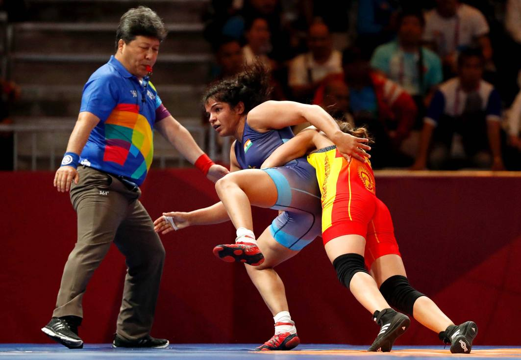 Aisuluu Tynybekova of Kyrgyzstan in action with Sakshi Malik of India at the Women's Freestyle 62 kg Semifinal in Jakarta, Indonesia, Reuters/UNI