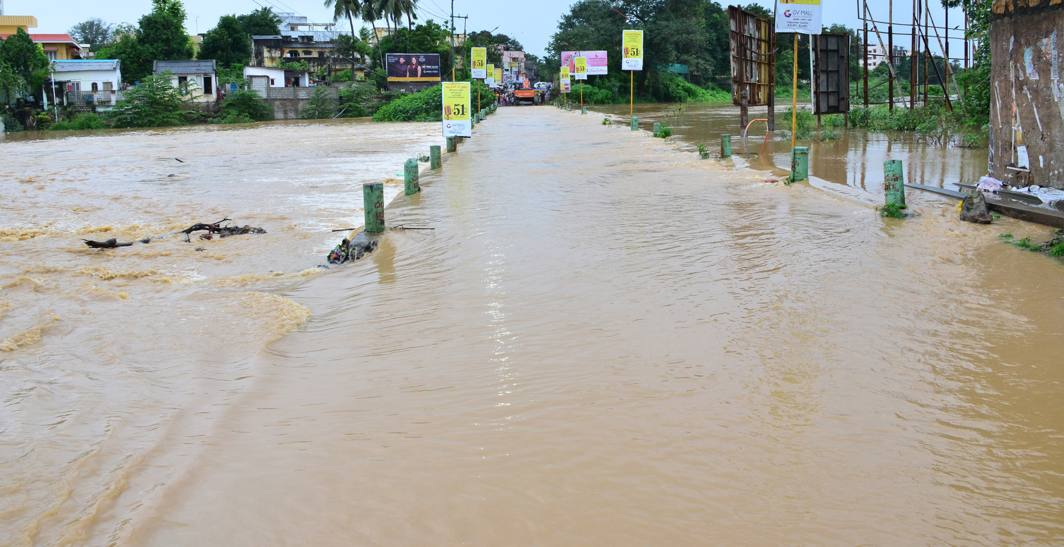 A view of the flood water overflowing the bridge disrupting transportation to Sanivarapupet village, as the Tammileru is in spate following heavy rains in catchment areas for the last two days, in Eluru district, UNI