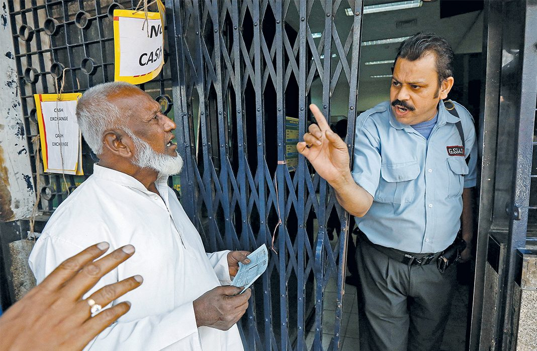 A security guard trying to close the door against people queuing outside a bank in Kolkata. Photo: UNI