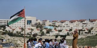 A teacher gives a class to Palestinian bedouin students outdoors near the Jewish settlement of Maale Adumim (seen in the background), in the West Bank village of Al-Eizariya, east of Jerusalem. Photo: UNI