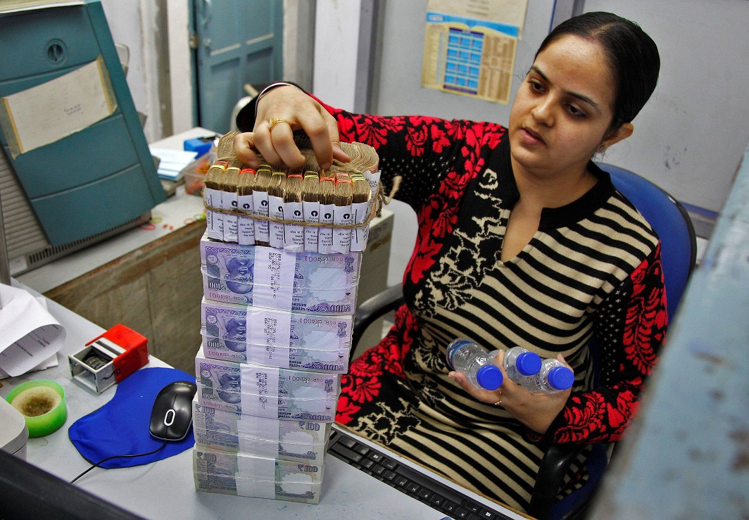 A cashier stacks Indian currency notes inside a bank in Chandigarh. Photo: UNI