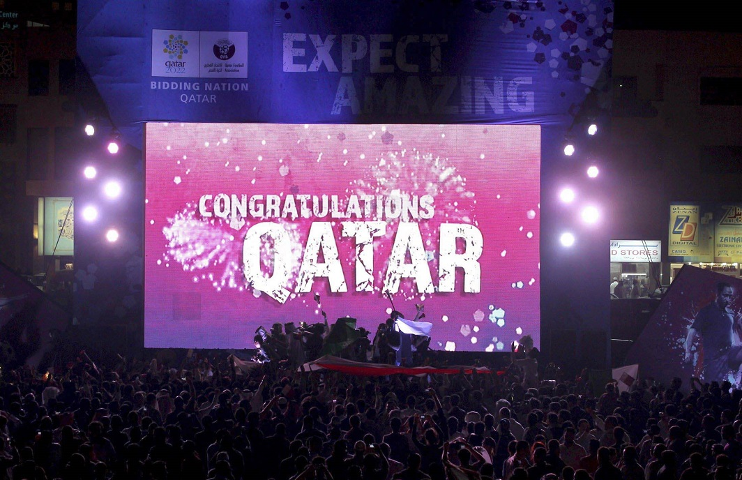 """People celebrate in front of a screen that reads """"Congratulations Qatar"""" after FIFA announced that Qatar will be host of the 2022 World Cup in Souq Waqif in Doha (file photo). Photo: UNI"""