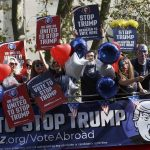 "Campaigners hold placards on a ""Stop Trump"" bus before touring London to urge Americans living abroad to register and vote. Photo: UNI"