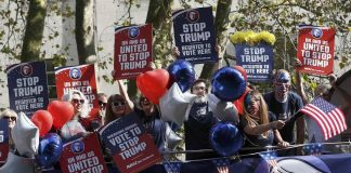 """Campaigners hold placards on a """"Stop Trump"""" bus before touring London to urge Americans living abroad to register and vote. Photo: UNI"""