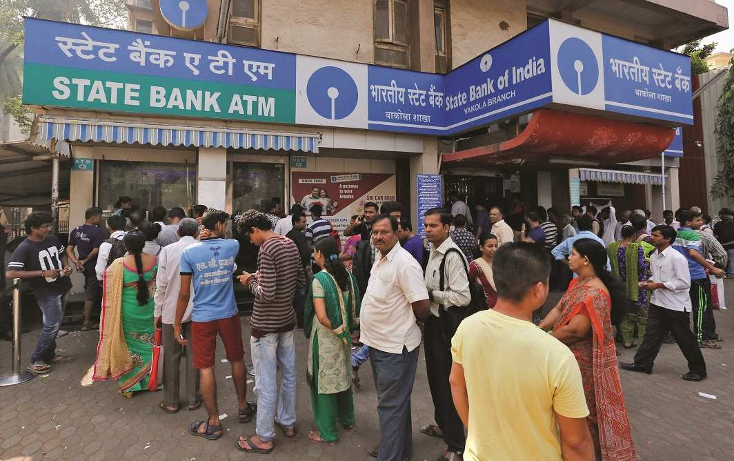 People queue up to exchange or deposit old notes outside a bank in Mumbai. Photo: UNI