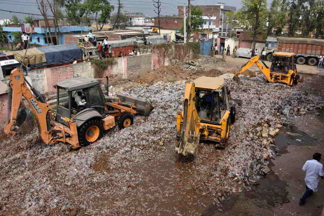JCB machines crushing the bottles of country made liquor at Danapur in Patna. Photo: UNI