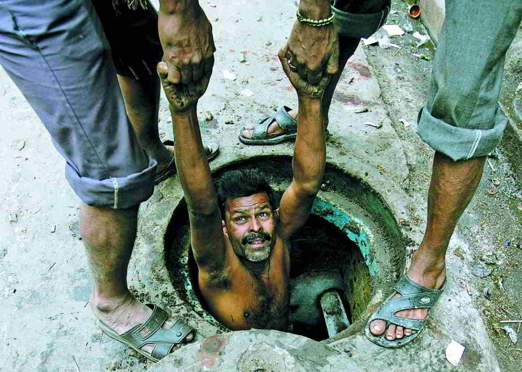 A labourer is lowered to clean sewage in Kolkata