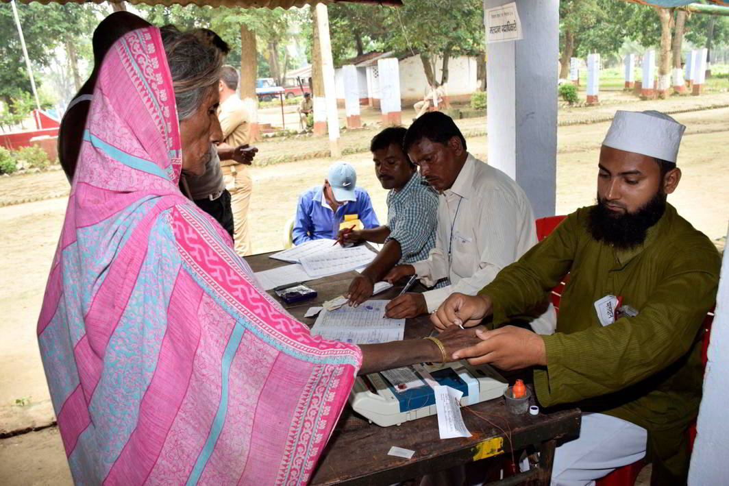 A polling officer applies ink mark on the finger of a voter at a polling station in Bihar. Photo: UNI