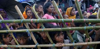 Rohingya refugees look through a fence as they wait outside of aid distribution premises at a refugee camp. Photo: UNI