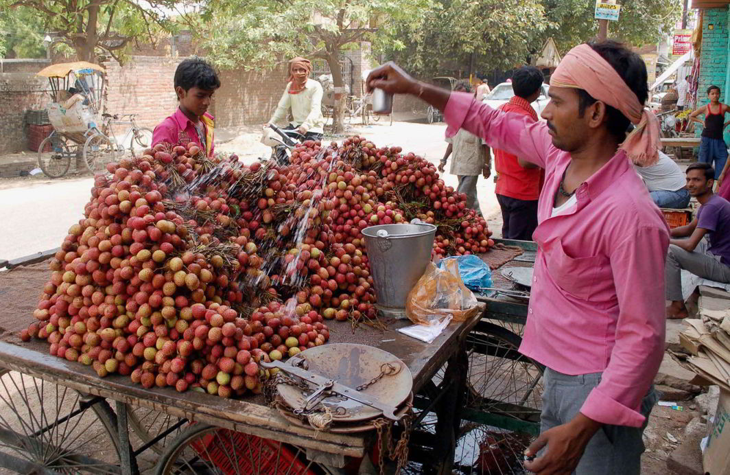 A roadside hawker pours water on litchis to keep it fresh (file picture). Photo: UNI