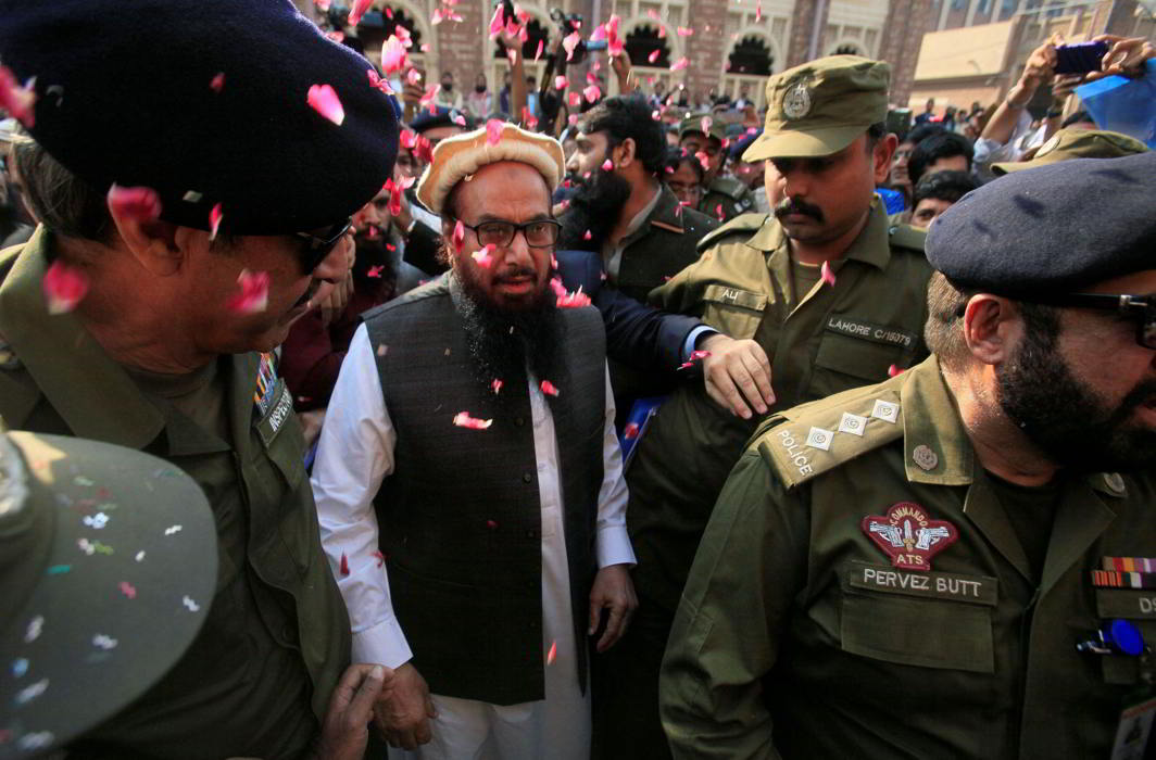Hafiz Saeed is showered with flower petals as he walks to court before his release order. Photo: UNI