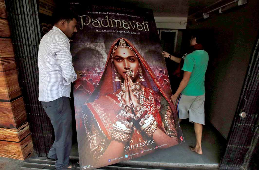 Workers carry a poster advertising upcoming Bollywood film Padmavati. Photo: UNI