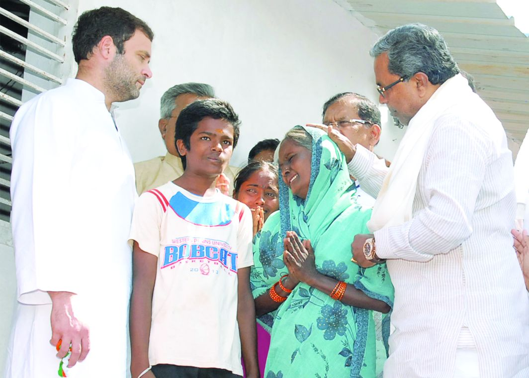 The widow of a farmer who committed suicide in Karnataka shares her troubles with Rahul Gandhi, the Congress president. Photo: UNI