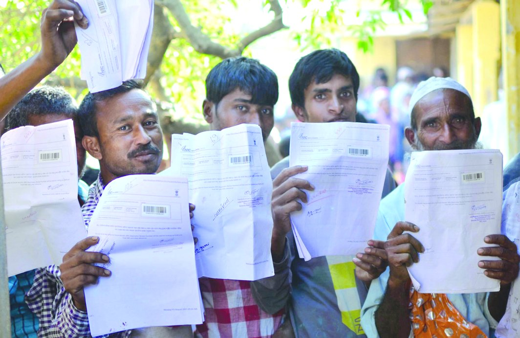 Villagers showing acknowledgement receipts of NRC registration at Gumi village in Kamrup district of Assam. Photo: UNI