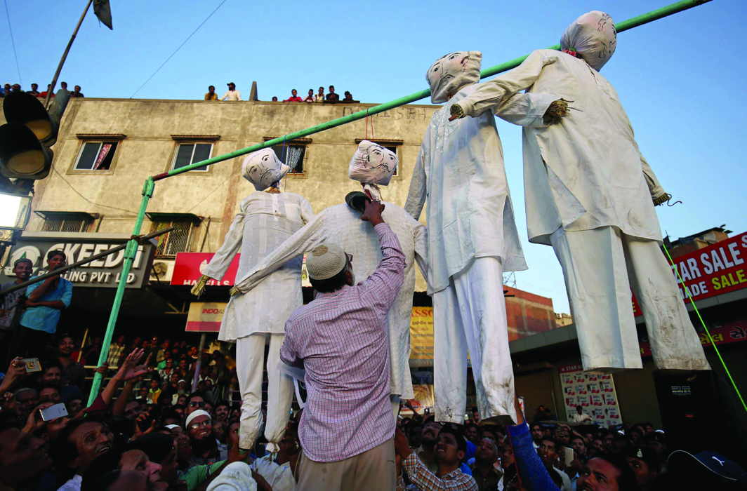 A man beats an effigy of a rapist at a protest against the rapes of minor girls/Photo: UNI