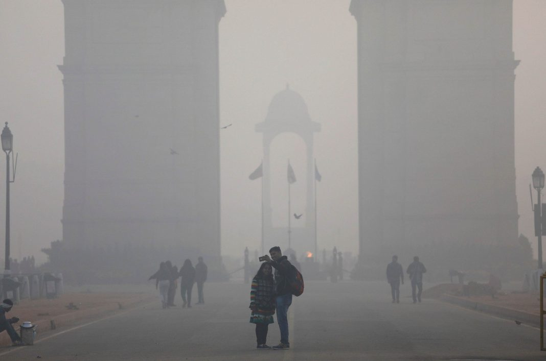 People take a selfie in front of the India Gate war memorial on a smoggy winter morning in New Delhi
