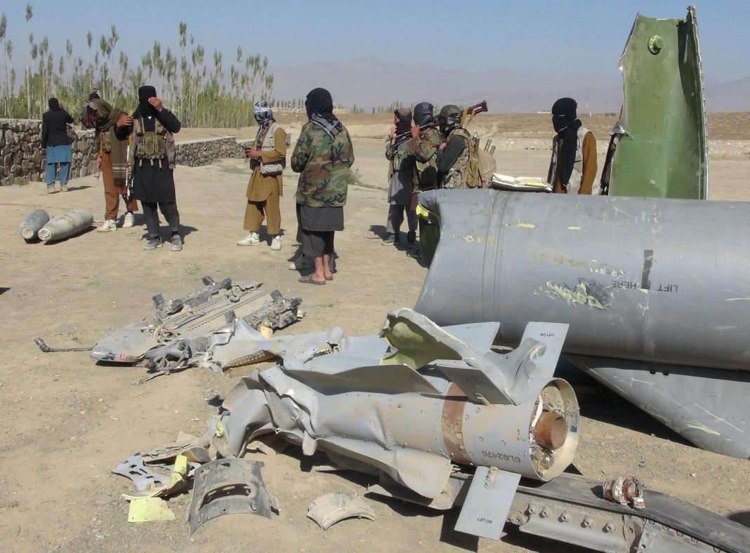 Taliban militants stand next to the wreckage of a damaged aircraft, in Sayed Karam district, Afghanistan/Photo: UNI