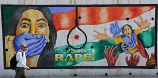 A man walks past graffiti depicting a message against rape of minors/Photo: UNI