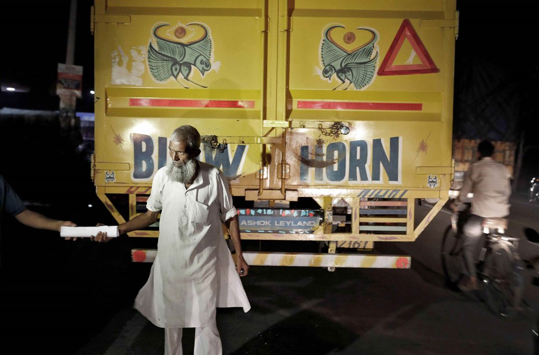 A truck driver handing over his transportation documents to cow vigilantes for inspection/Photo: UNI