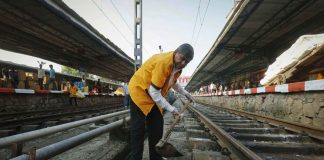 A worker cleans a railway track at a station in Mumbai. Many overqualified people apply for such menial jobs in government/Photo: UNI