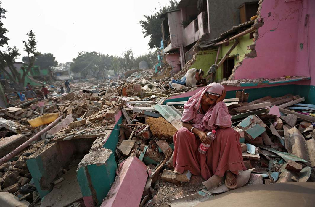A slum-dweller rests amid the rubble of her home, demolished by the authorities in Delhi/Photo: UNI