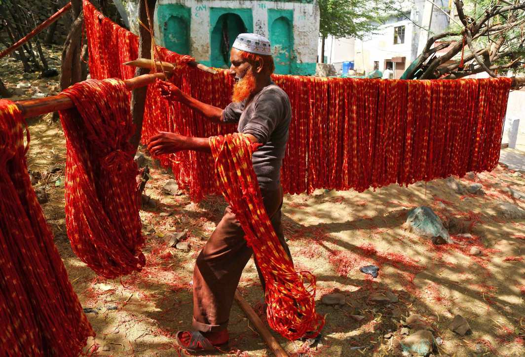 TO DYE FOR: A worker hangs kalavas or sacred threads to dry after dyeing them with colours in Ajmer, Reuters/UNI