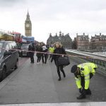 A woman ducks under police tape on Westminster Bridge after the attack