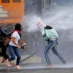 REVOLUTIONARIES: Demonstrators clash with riot security forces while rallying against Venezuela's President Nicolas Maduro's Government in Caracas, Reuters/UNI
