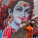 SHIVA'S LOYAL: A kanwaria shelters from the rain in front of a poster of Lord Shiva in New Delhi, Reuters/UNI