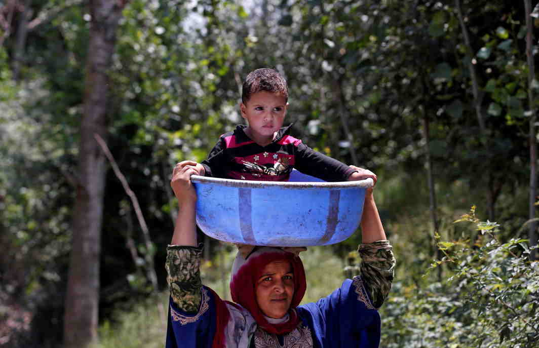 JOY RIDE: A woman carries a child in a plastic container through a road at Tantray Pora in south Kashmir's Kulgam district, Reuters/UNI