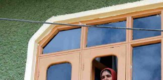 SILENT SENTINEL: A girl peeps through a window during raids by the National Investigation Agency in connection with a terror funding case, in Srinagar, UNI