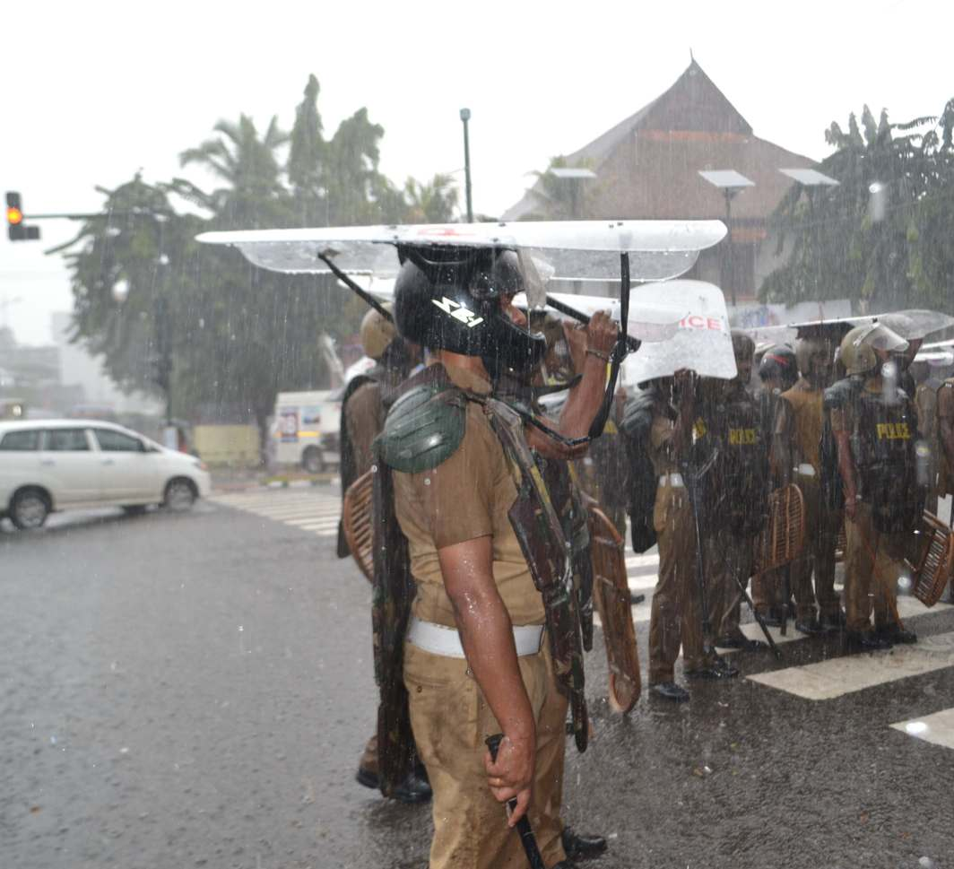 DRENCHED NONETHELESS: Police personnel use their shields as umbrellas as heavy rain lashes Thiruvananthapuram city, UNI