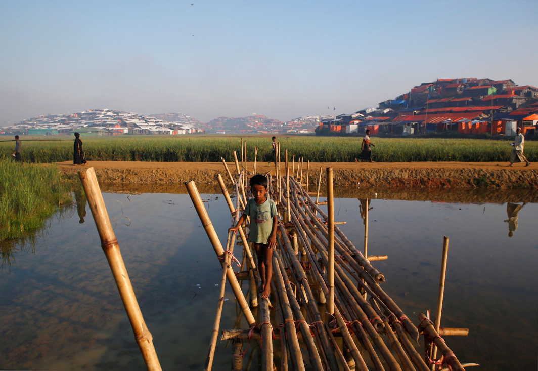 CHILD'S BLISS: A Rohingya refugee boy walks on a bamboo bridge at Palong Khali refugee camp near Cox's Bazar, Bangladesh, Reuters/UNI
