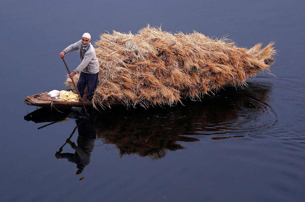 WET TRANSPORT: A man rows his boat filled with straw on the waters of Nageen Lake on a cold morning in Srinagar, Reuters/UNI