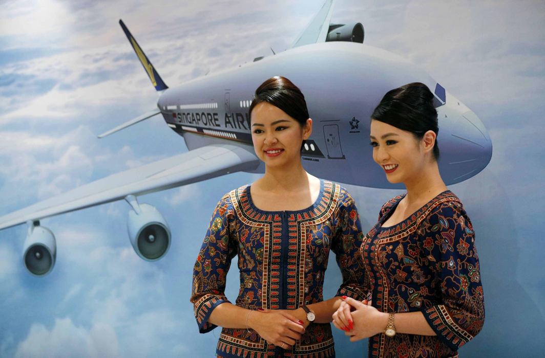 HIGH FLIERS: Flight attendants pose for photos at a presentation of Singapore Airlines' newly launched cabin products in Singapore, Reuters/UNI