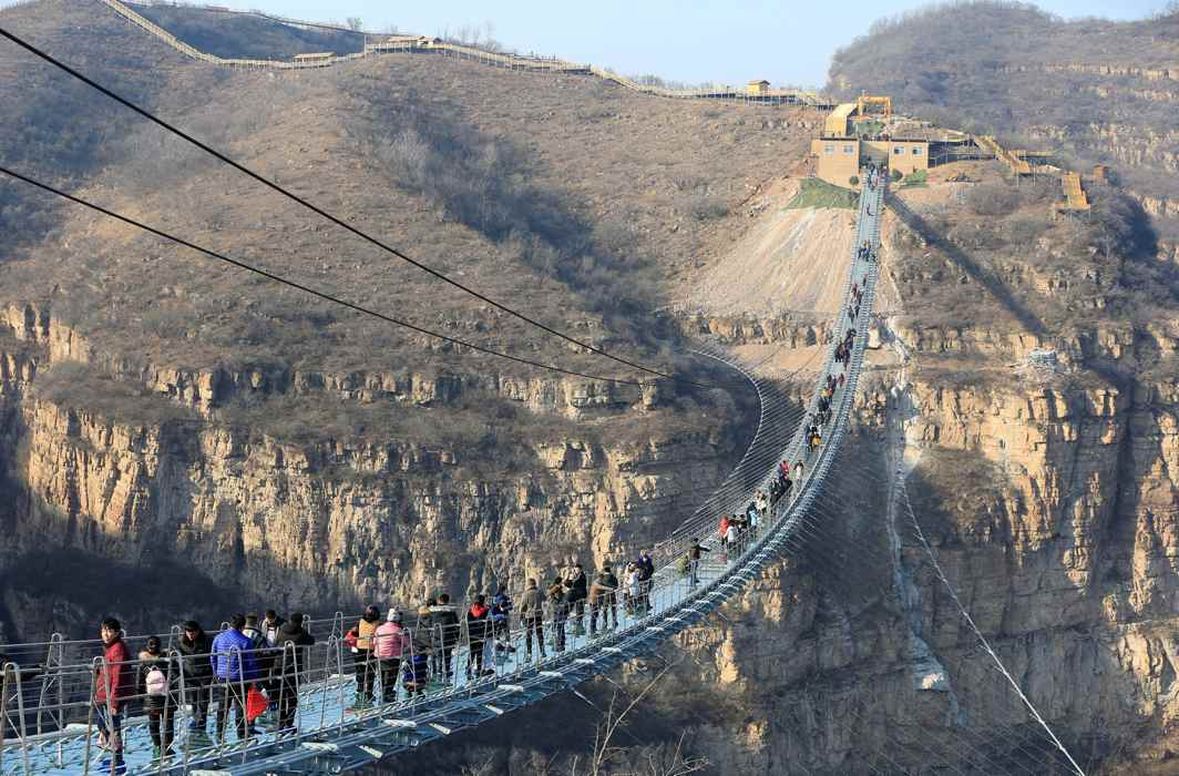 SCENIC WALK: Visitors walk on the newly-opened 488-metre-long glass suspension bridge at Hongyagu attraction in Pingshan, Hebei province, China, Zhang Haiqiang/Reuters/UNI