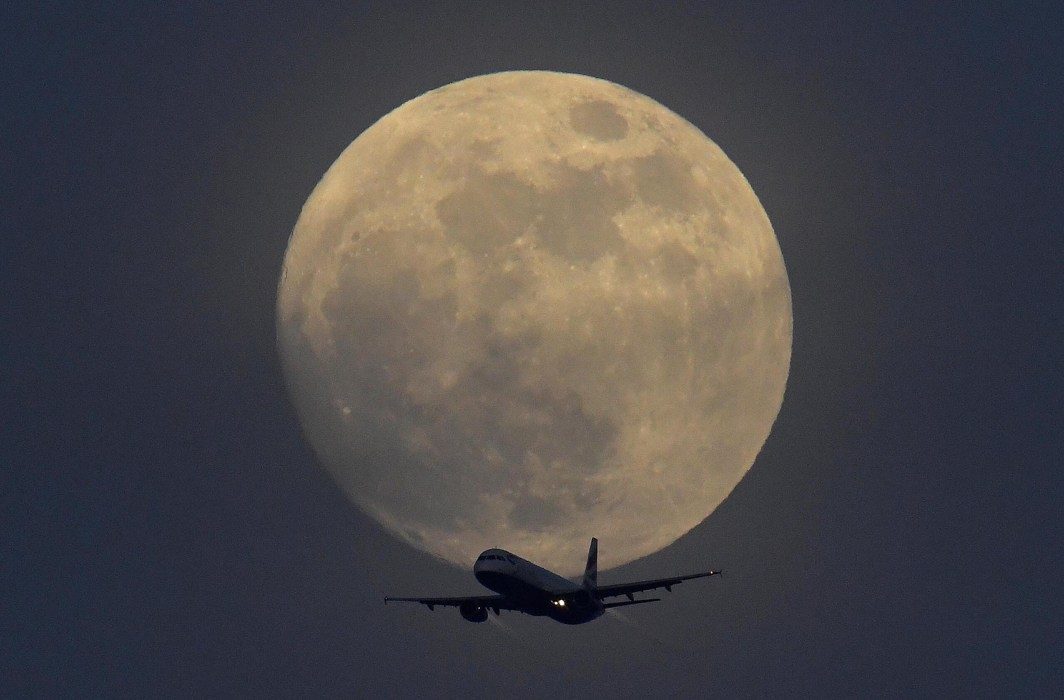 FLY AWAY: A British Airways aircraft flies in front of a full moon over London, Britain, Reuters/UNI