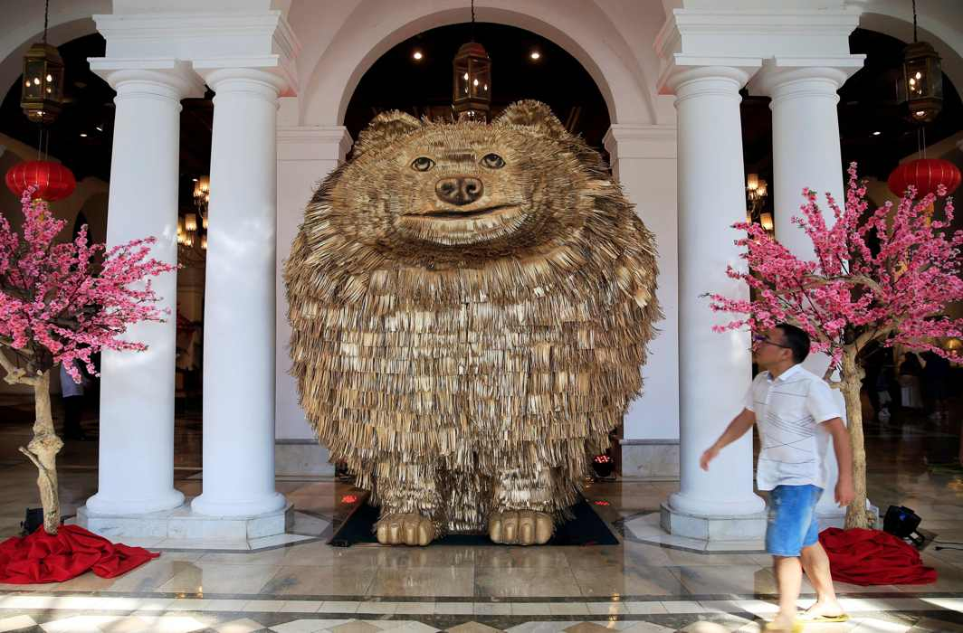 LARGER THAN LIFE: A hotel guest looks at a Pomeranian dog-shaped statue displayed at a hotel, ahead of the Chinese Lunar New Year of the Dog in Metro Manila, Philippines, Reuters/UNI