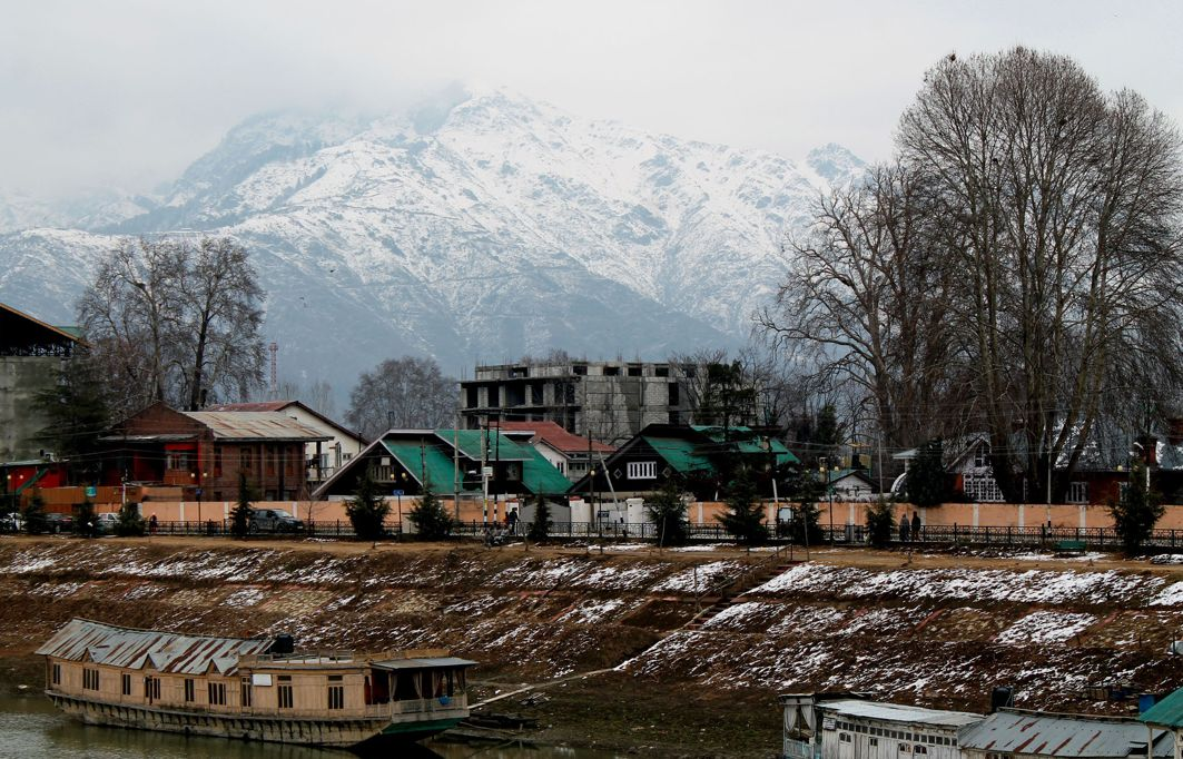 FIRST DAY OF SPRING: Houseboats on the Jhelum in the backdrop of snow-clad Zabarwan Hills, in Srinagar, UNI