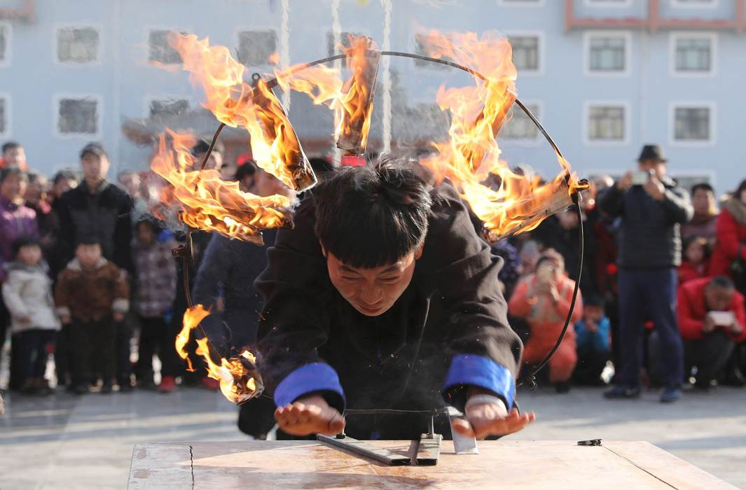 NEW YEAR BRAVERY: A man performs a stunt through a ring of fire during a traditional folklore performance ahead of the Chinese Lunar New Year, or Spring festival, at Chenjiagou village in Wen county, Henan province, China, Reuters/UNI