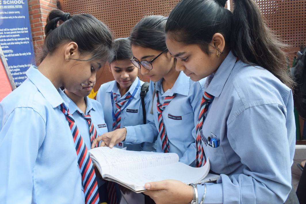 BEST OF LUCK: Students busy in last minute preparations outside an examination centre, on the first day of the beginning of the CBSE board exams, in New Delhi, UNI