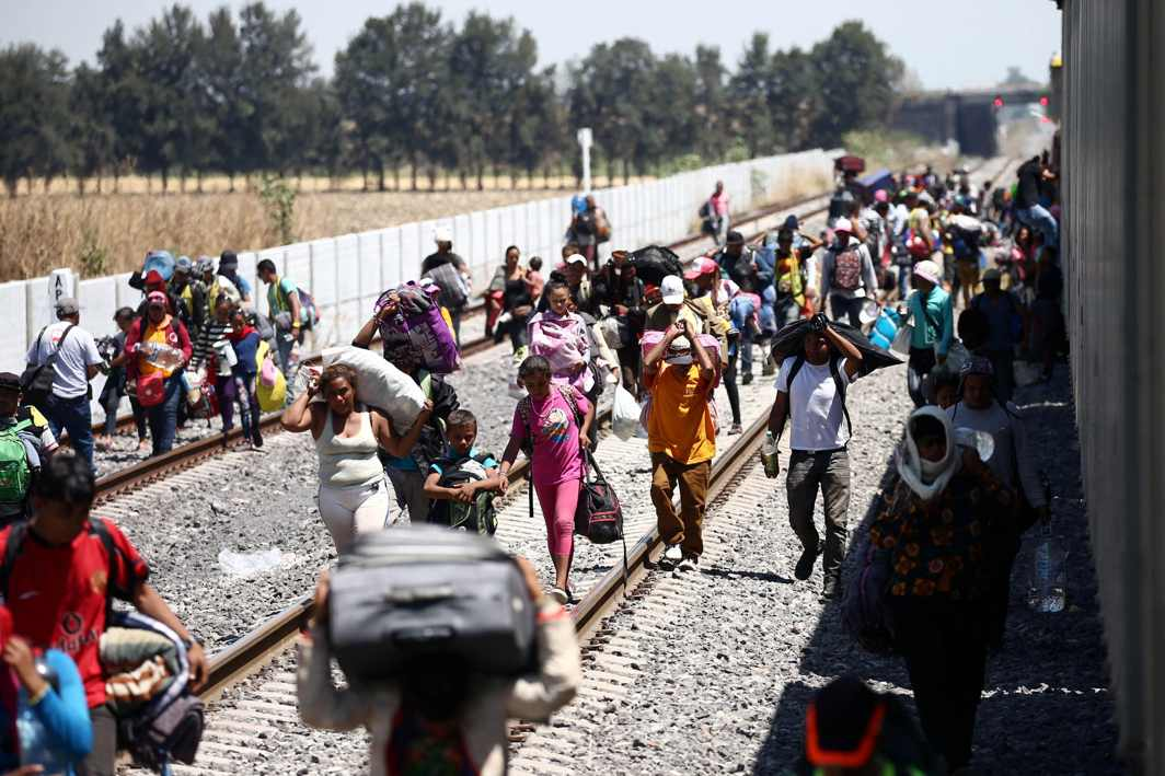 LONG MARCH: Central American migrants, moving in a caravan through Mexico, disembark from a freight train as they walk on a railway track after stopping the train on a rail line, in Irapuato, Guanajuato state, Mexico, Reuters/UNI