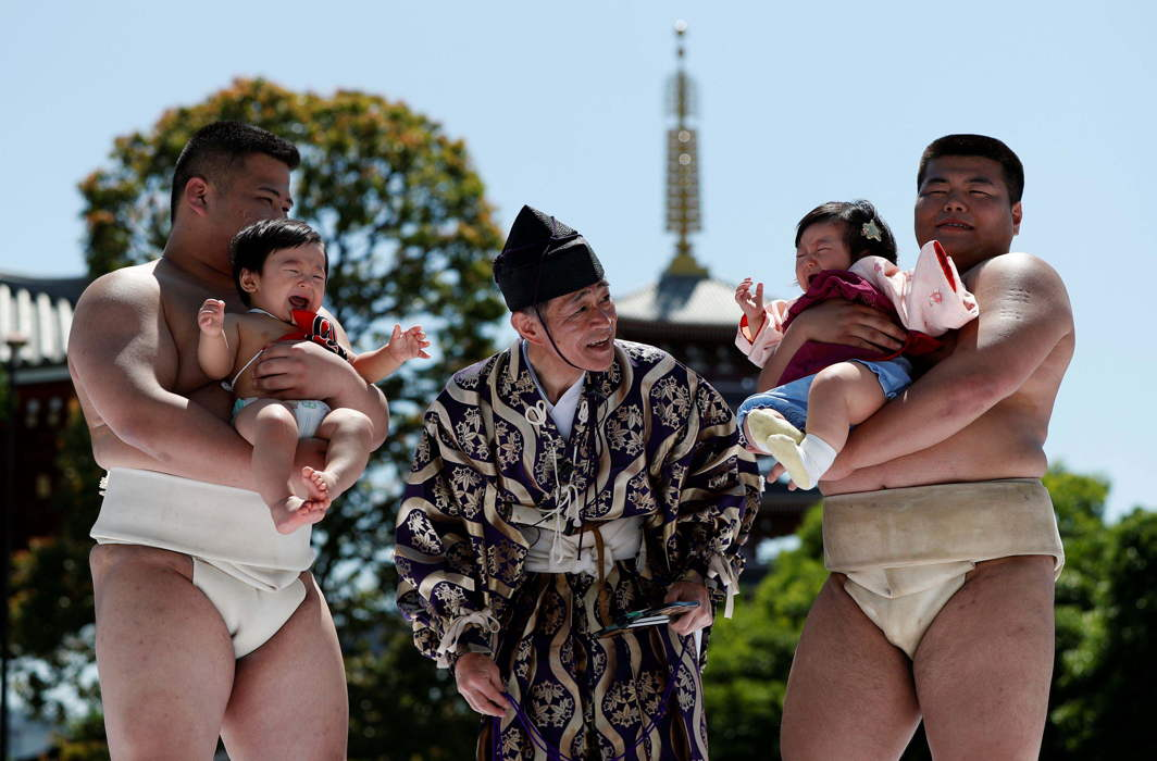LOUD AND PROUD: Babies, 9-month-old Kizuki (L) and 10-month-old Sarah, cry as they are held up by amateur sumo wrestlers during a baby crying contest at Sensoji temple in Tokyo, Japan. In the contest two wrestlers each hold a baby while a referee makes faces and loud noises to make them cry. The baby who cries the loudest wins, Reuters/UNI