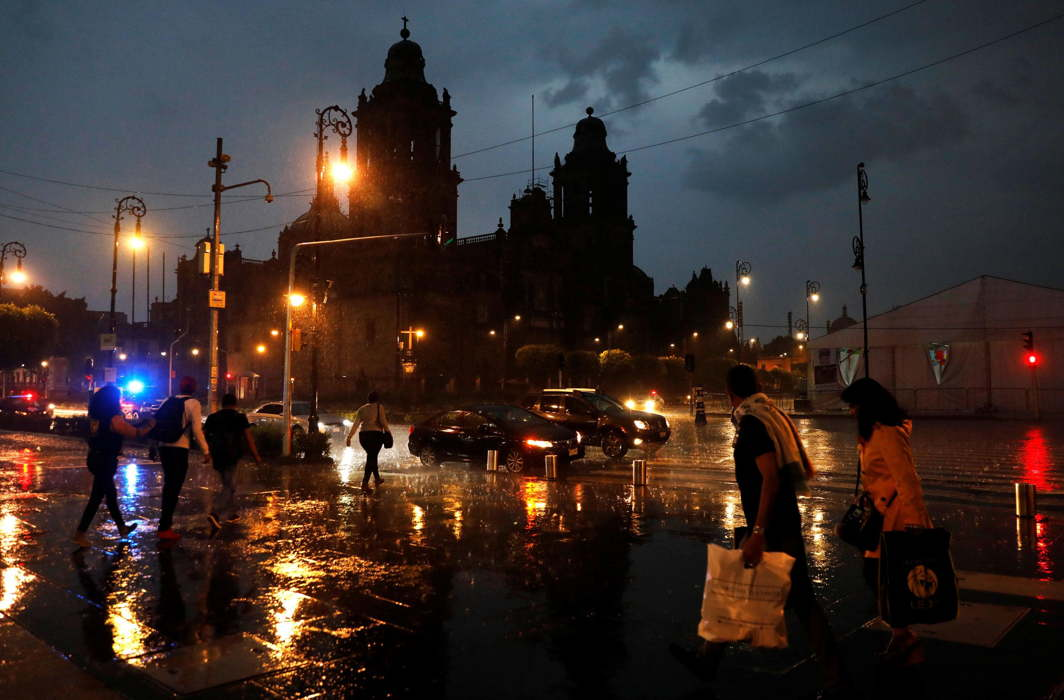CITY BREATHES: People walk in the rain next to the cathedral in downtown Mexico City, Mexico, Reuters/UNI