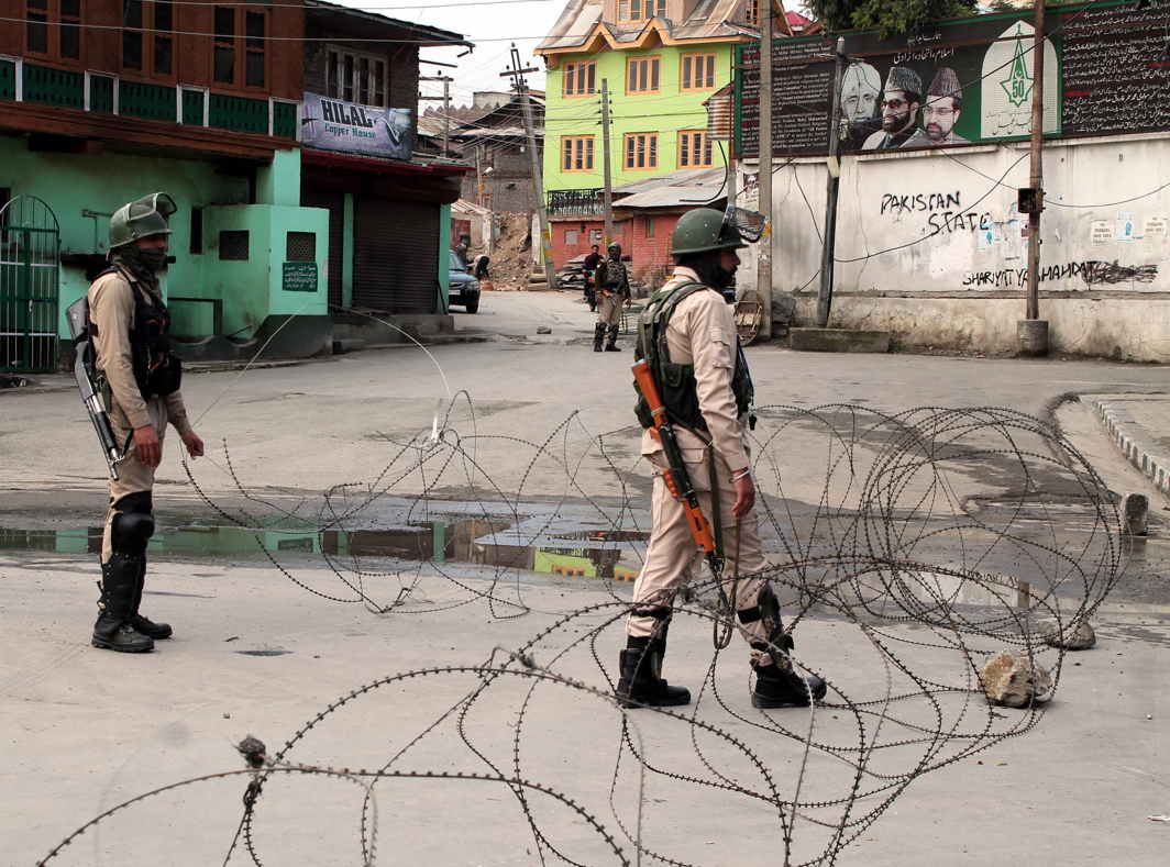 Security forces behind the concertina razor wire near Mirwaiz Manzil in a curfew-bound area of Rajouri Kadal in downtown Srinagar, UNI